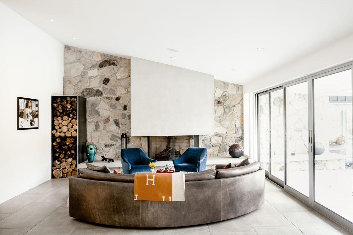 A large stone fireplace has a pale hood. A curved leather sofa sits in front of it.