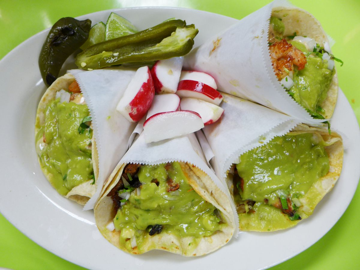 Three tacos rolled up in tissue paper dressed with green guacamole.