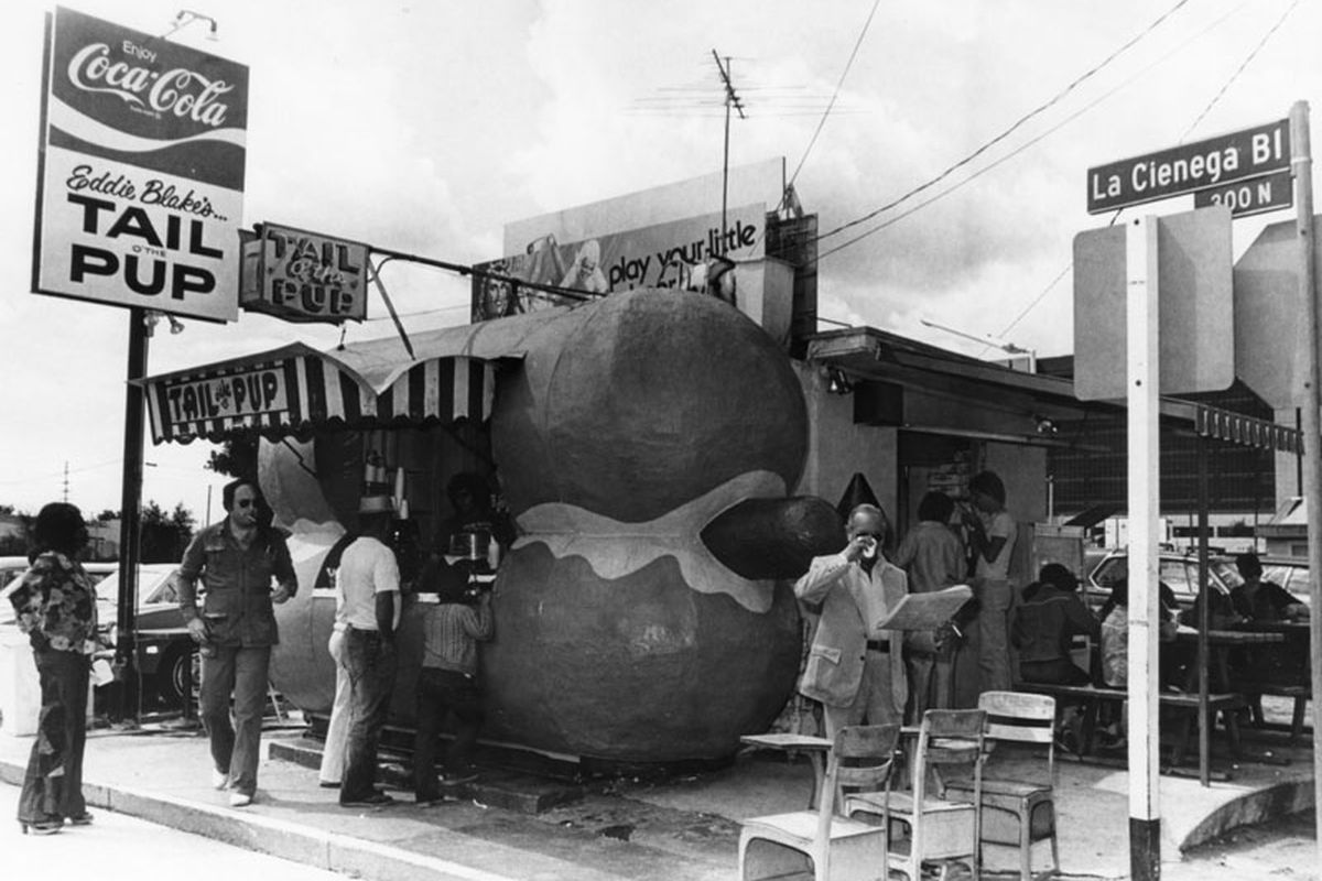 A black and white photo of an old hot dog stand with people waiting to order. The stand is shaped itself like a hot dog.