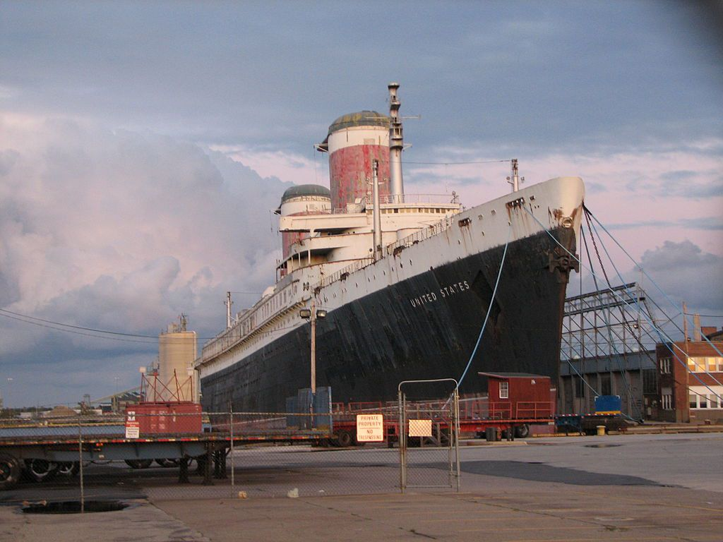 The exterior of the ship SS United States. The ship is parked at a dock. It has two large smoke stacks on it.