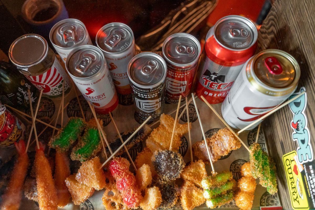 Plastic kushikatsu alongside cans of beer and sake at Taku.