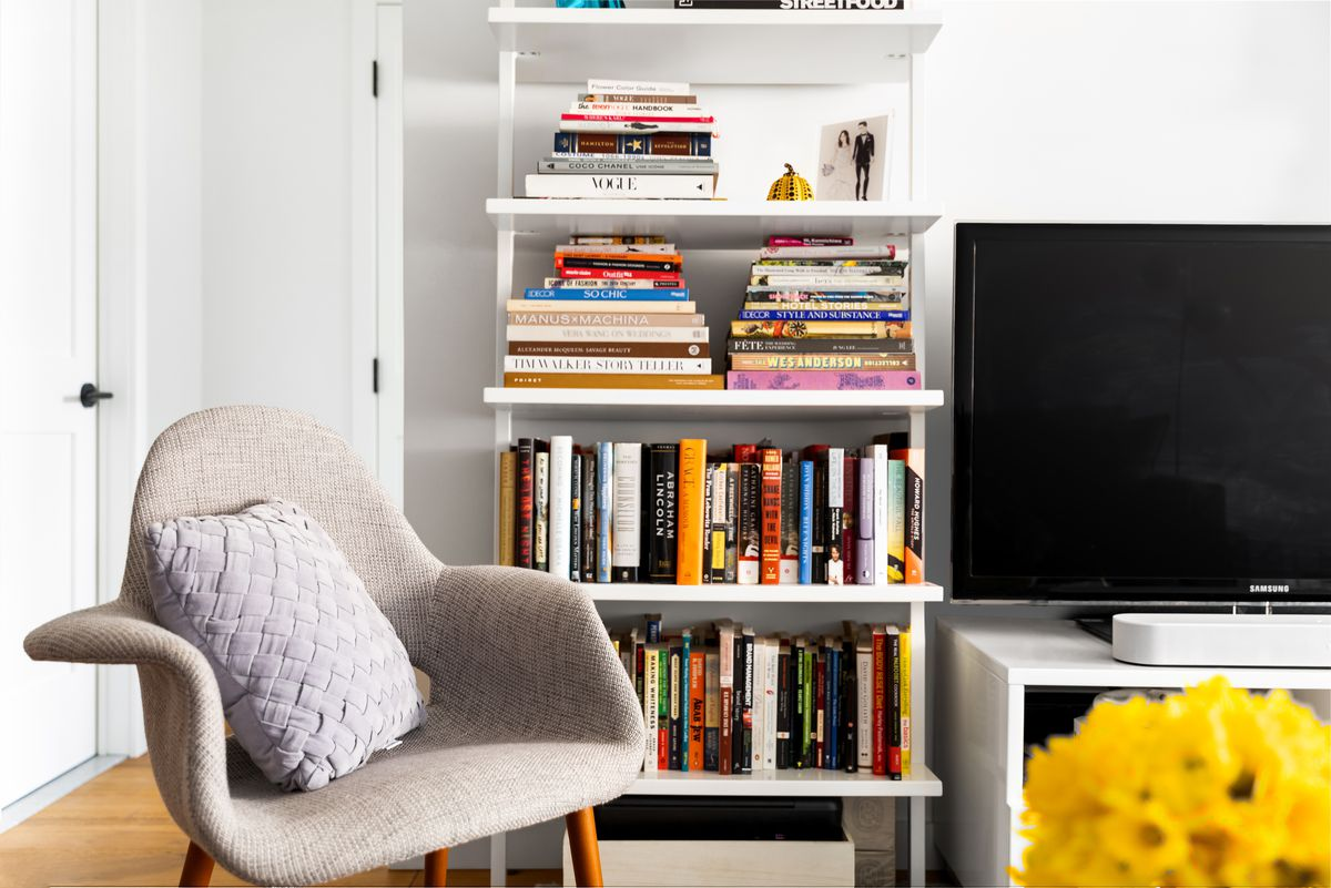 A white bookshelf next to a TV on a white stand and a beige chair.