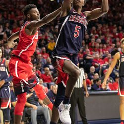 Brandon Randolph (5) twists in a shot past Dylan Smith, left, during the 2018 Red-Blue game in McKale Center on October 14 in Tucson, Ariz.