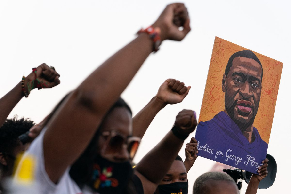 A group of people each raise a fist while one holds up a picture of George Floyd's face.
