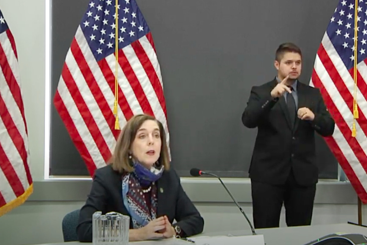 Kate Brown sits in front of American Flags at a press conference
