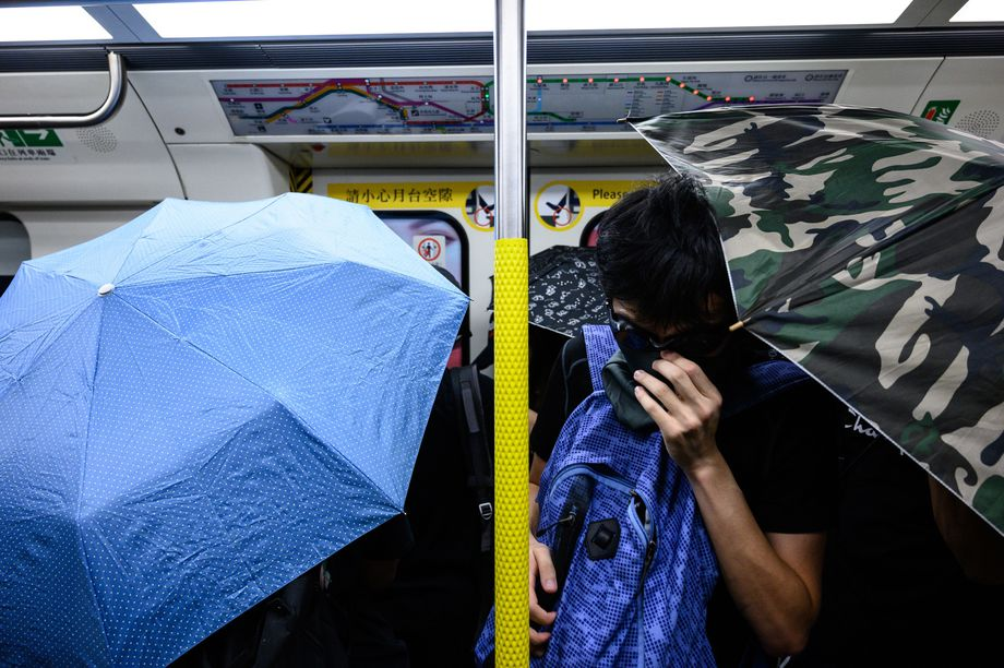 Protesters hold open umbrellas inside a train during a September 2 protest.