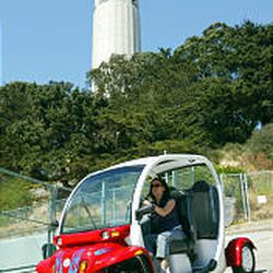 Vanessa Holland drives the Global Electric Motorcar, which is smaller than a golf cart, down Telegraph Hill below Coit Tower in San Francisco.