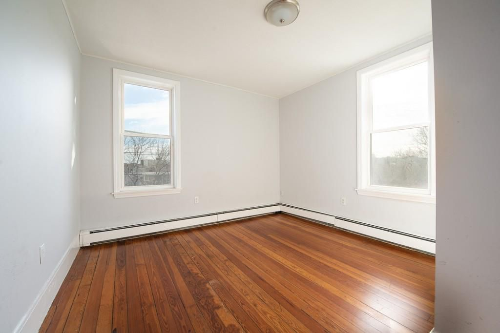 A small empty bedroom with a couple of windows.