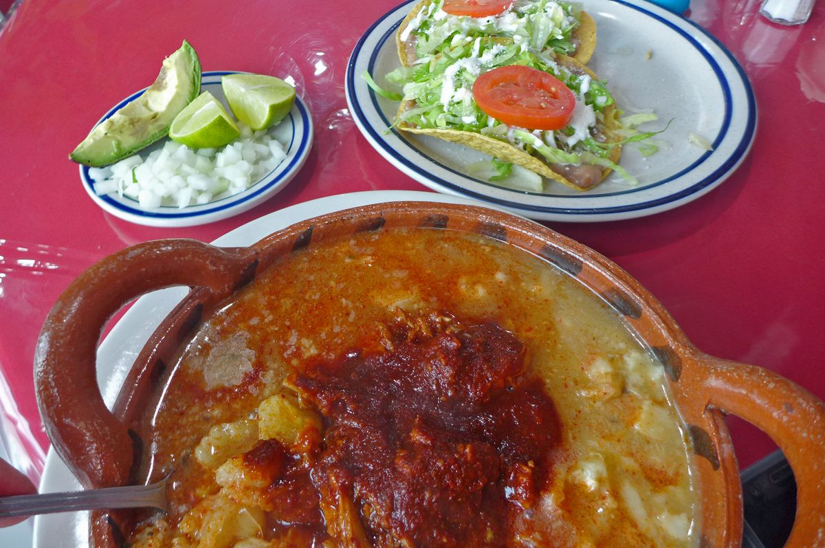 A bowl of fiery red soup with a pair of tostadas in the background and plate of rice and beans on the side...