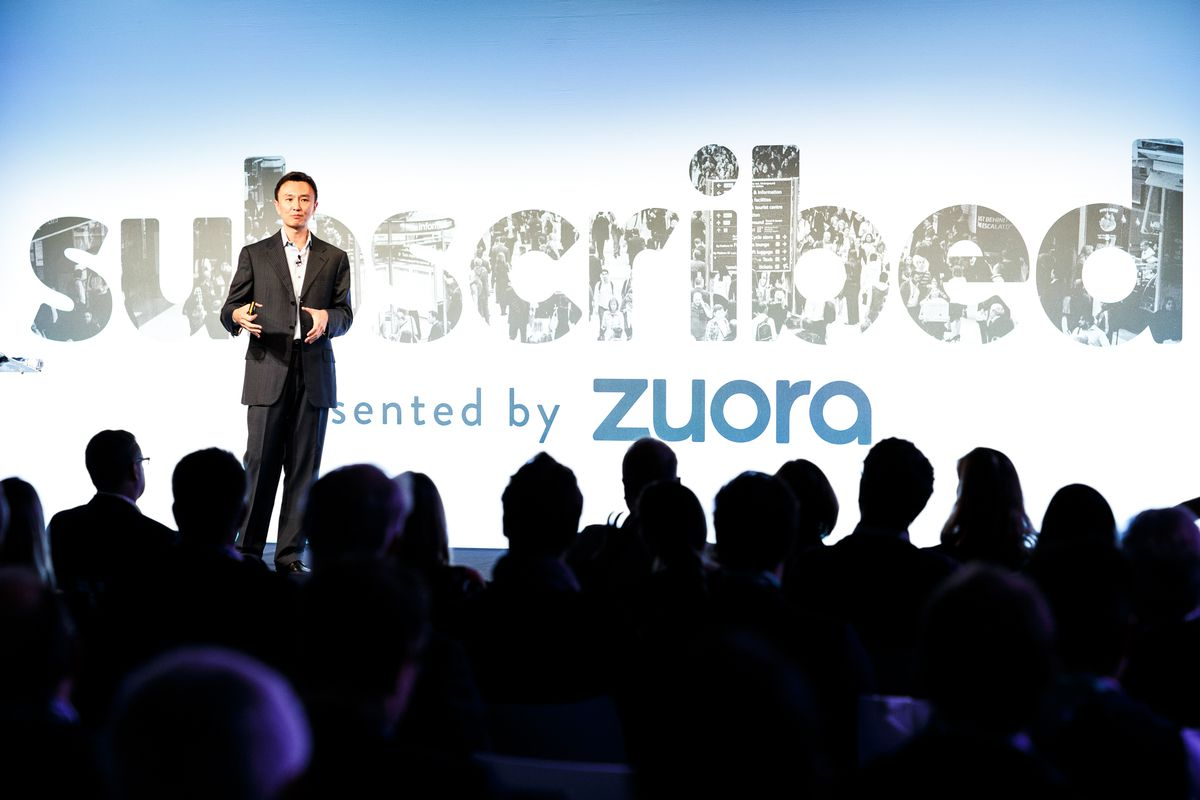 """Zuora CEO Tien Tzuo speaks onstage at a conference. Behind him, the screen reads, """"Subscribed, presented by Zuora."""""""