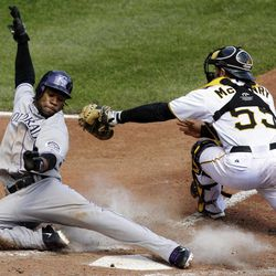 Colorado Rockies' Eric Young Jr., left, slides around the tag by Pittsburgh Pirates catcher Michael McKenry in the eighth inning of a baseball game in Pittsburgh, Wednesday, April 25, 2012. Young scored from third on a sacrifice fly to right field by Rockies' Tyler Colvin. The Rockies won the first game of the double header 2-1.