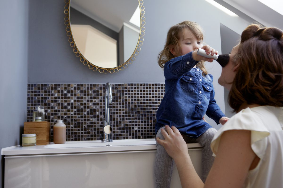 Toddler putting blush on mother's face