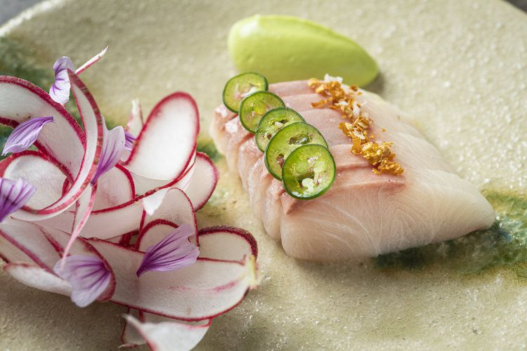 Slices of light pink raw fish, topped with jalapeno and accompanied by thin, oblong pieces of radish