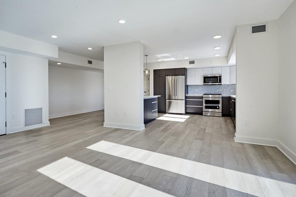 A spacious and empty living room-kitchen area in a new condo.