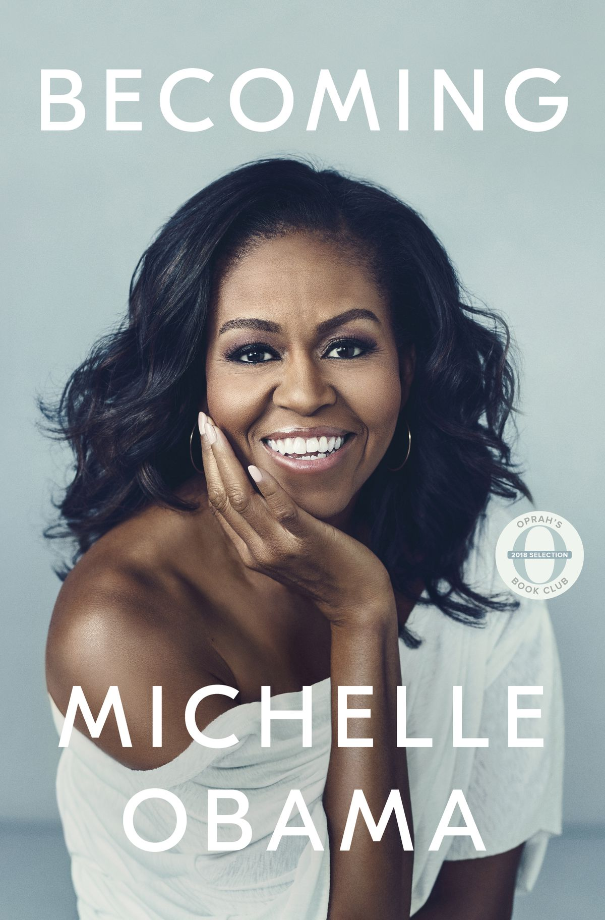 The cover is a portrait of Obama, smiling and wearing a white off-the-shoulder top against a pale blue background.