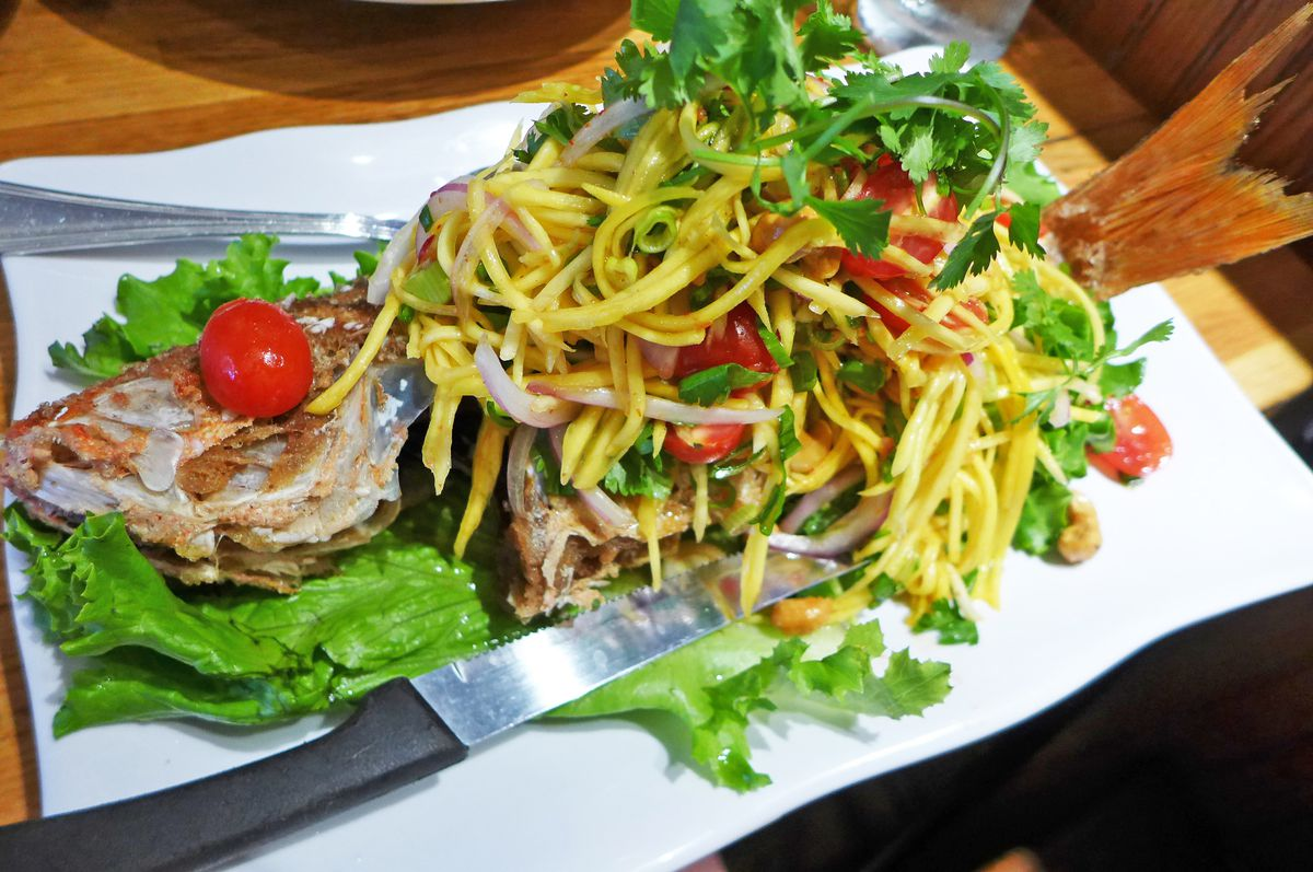 A whole fish topped with papaya salad