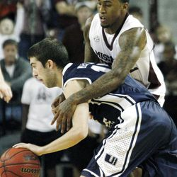 Mississippi State guard Dee Bost (3) reaches around Utah State guard Preston Medlin (13) as he tries to steal the ball in the second half of their NCAA college basketball game in Starkville, Miss., Saturday, Dec. 31, 2011. Mississippi State won 66-64.