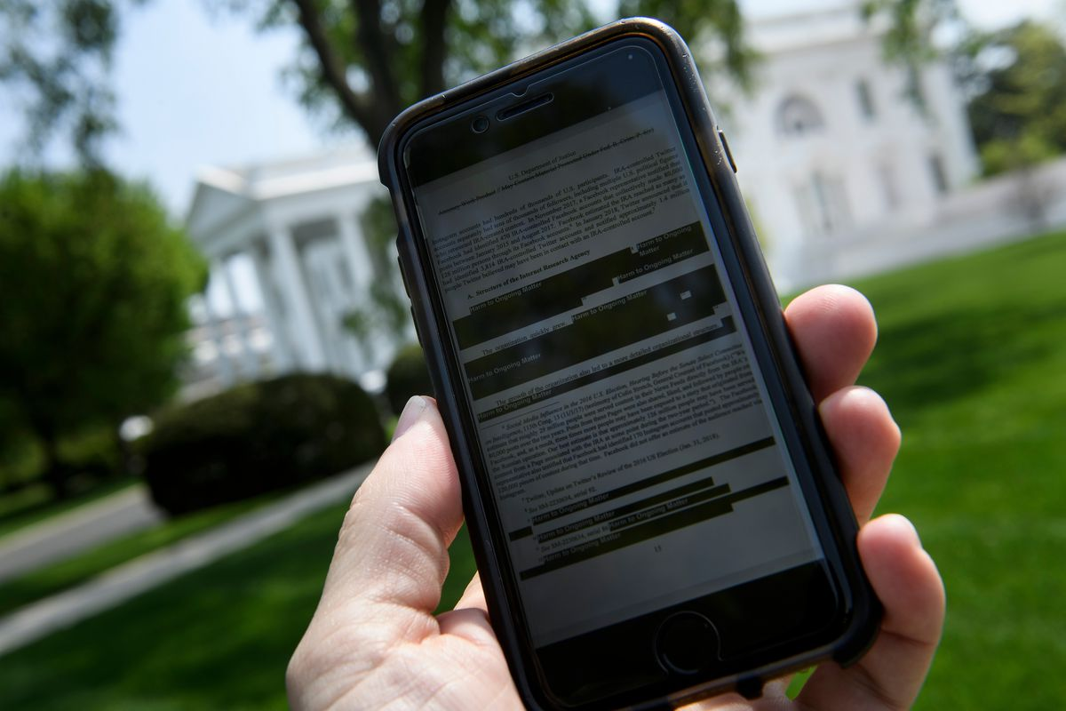 An electronic version of the Mueller Report with redactions regarding the Internet Research Agency as seen on a cellphone with the White House in the background.