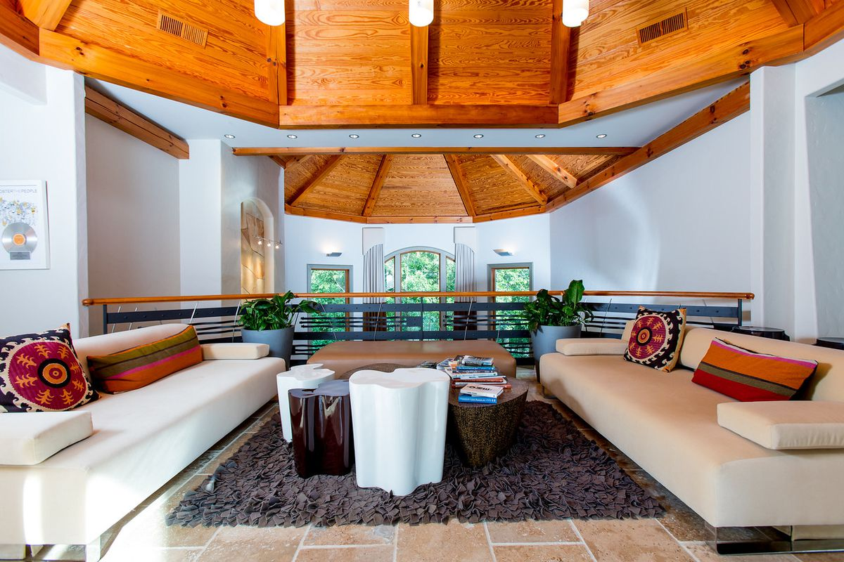 A large white lounge space with wood ceilings.