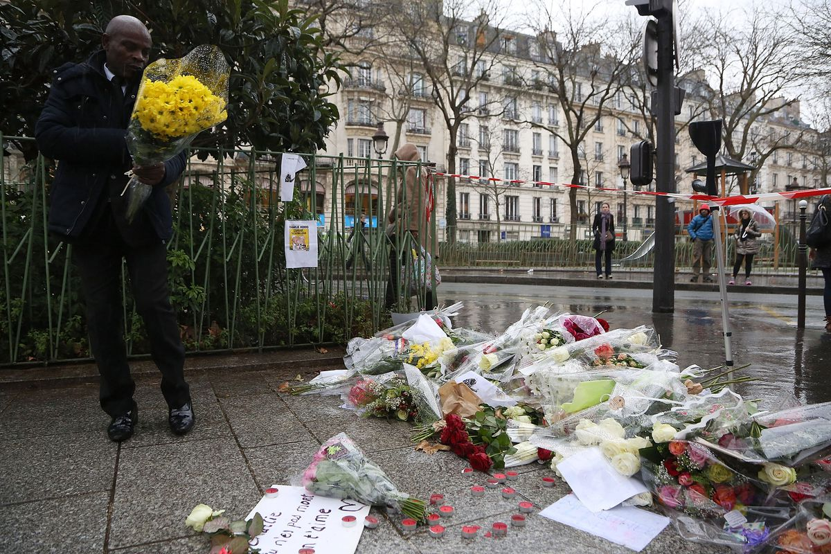 A man leaves flowers near the offices of Charlie Hebdo shortly after the attack that killed 12 people