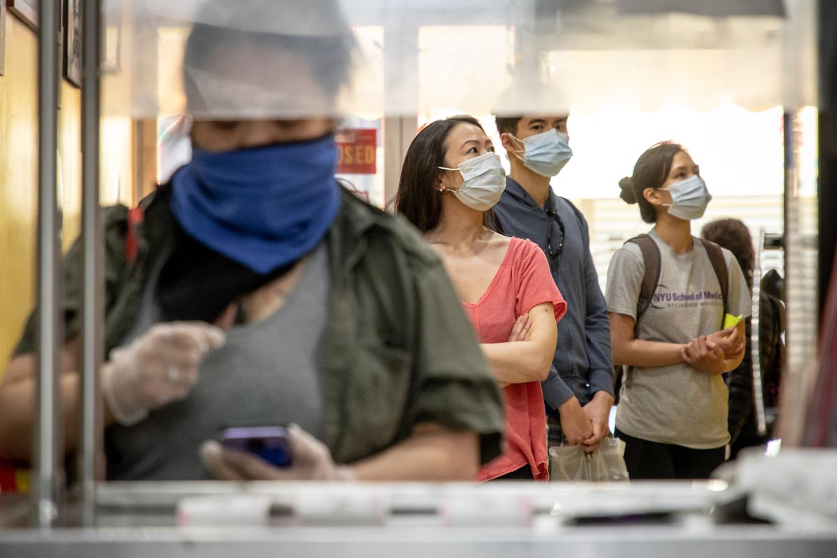 Four people in face masks read the menu and wait in line behind a restaurant counter.