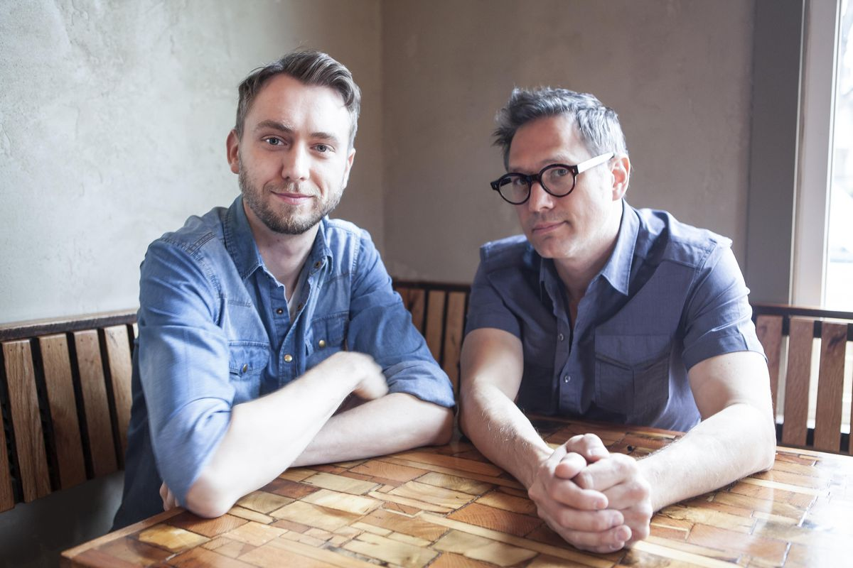 Corey Ladd and Matthew Spicher sit at a wooden table inside the restaurant