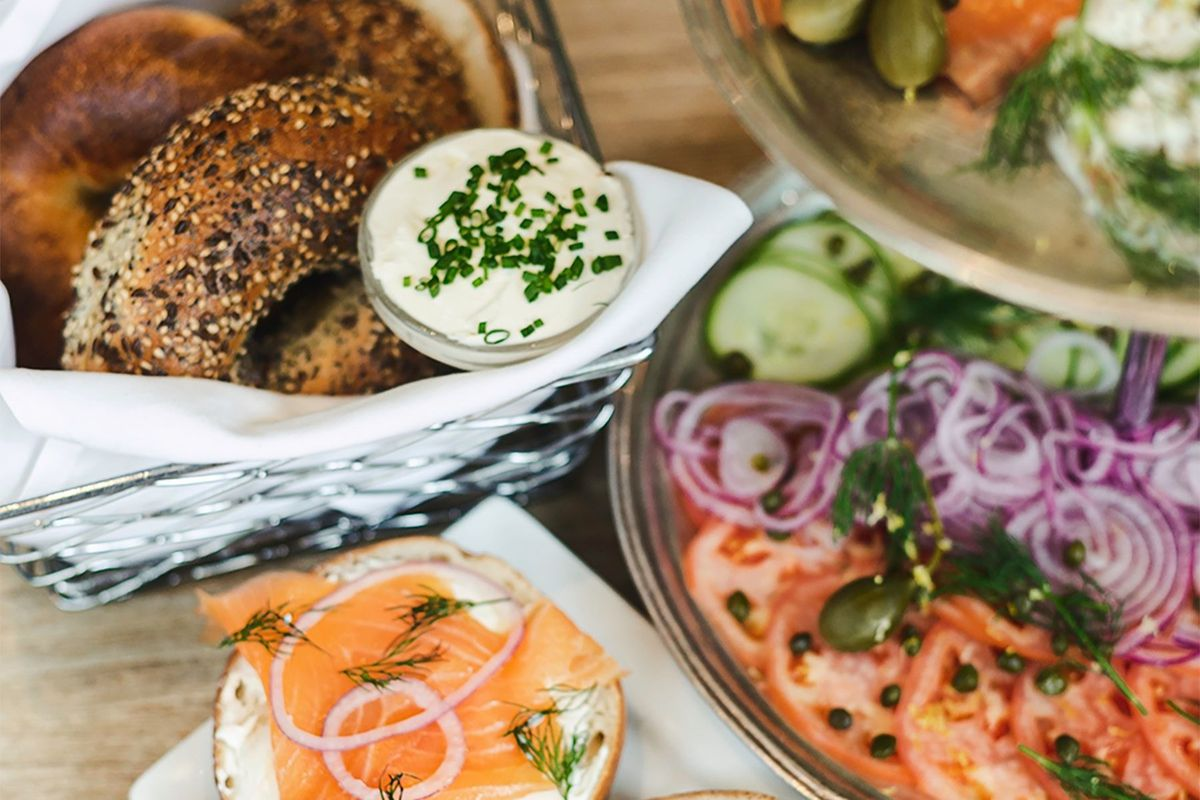 Cut bagels sit in a basket alongside a tower of toppings including red onion, cucumbers, and tomatoes, with an open-faced bagel topped with cream cheese and salmon sitting on a plate nearby