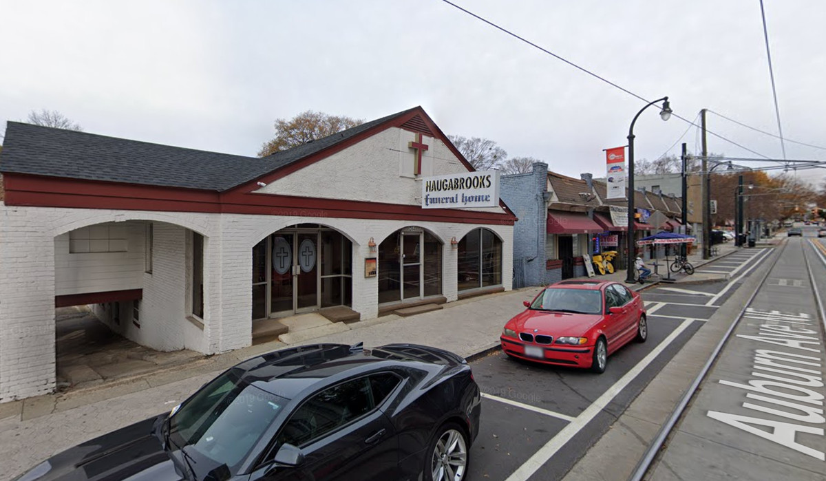 A streetcar track runs in front of an old funeral home and commercial spaces.