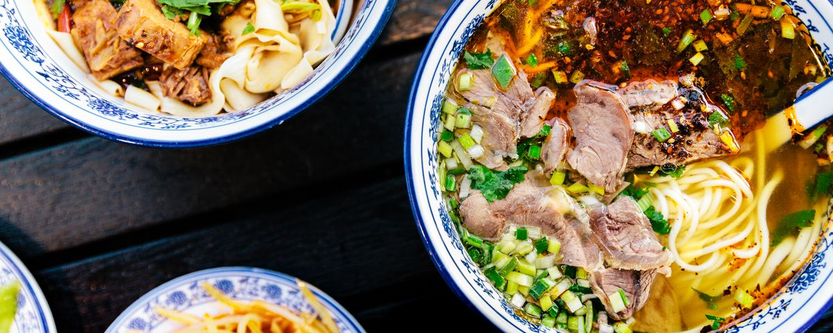 Two blue-rimmed white bowls of beef noodles sit atop a table next to a smaller blue plate of potatoes.