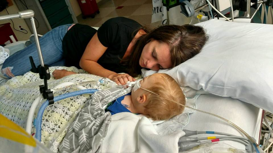 Jenny Bennett is lying next to her 18-month-old son, Jackson, on a hospital bed after his drowning accident. He did not survive.