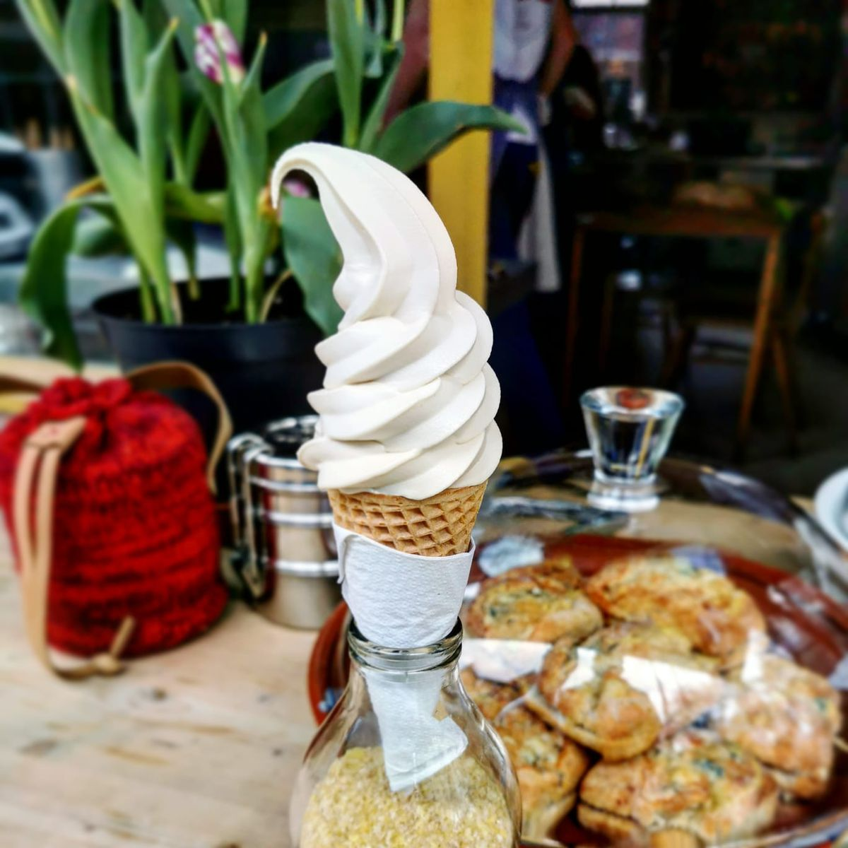 A cone of hazelnut soft serve sits in a glass bottle filled with sand, with pastries, a pot plant, and a red rattan fabric in the background