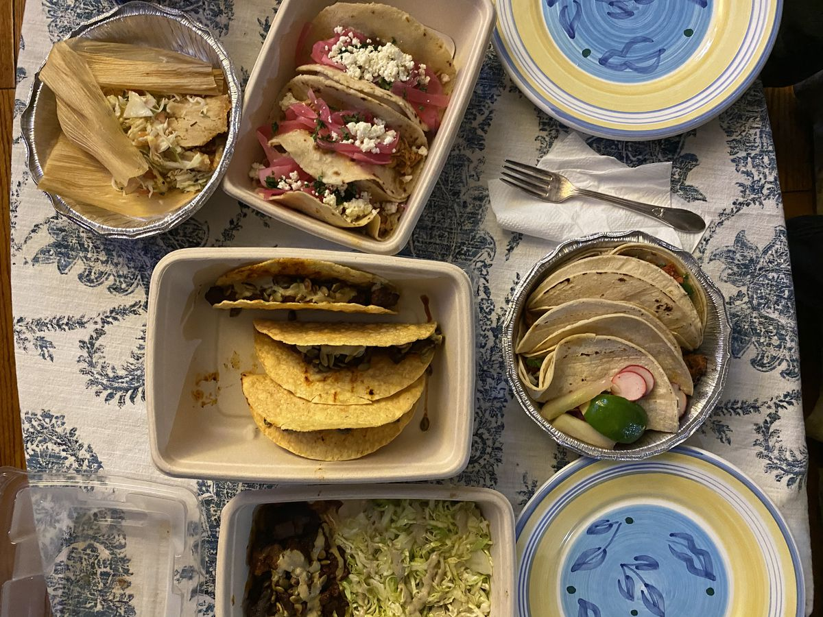 An assortment of tacos and tamales from Lourdes Mexican Grill and Taco Bay sit on a decorative blue and white tablecloth