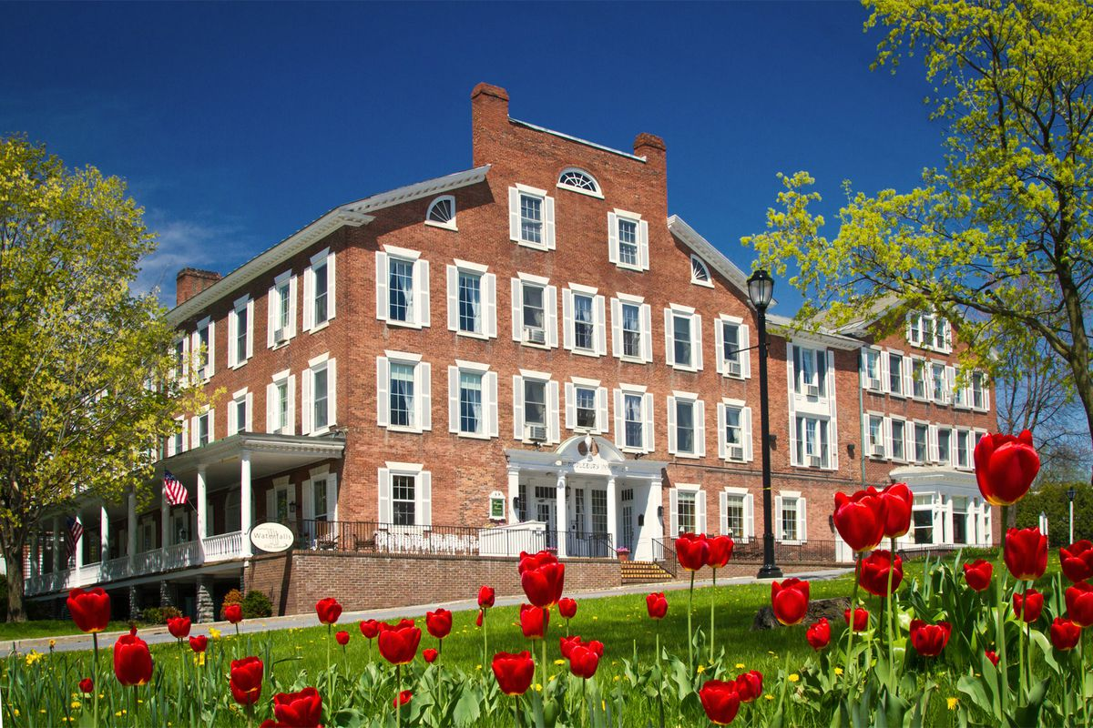 The exterior of the Middlebury Inn in Vermont. The facade is red brick with white shutters on the windows and a wraparound porch.