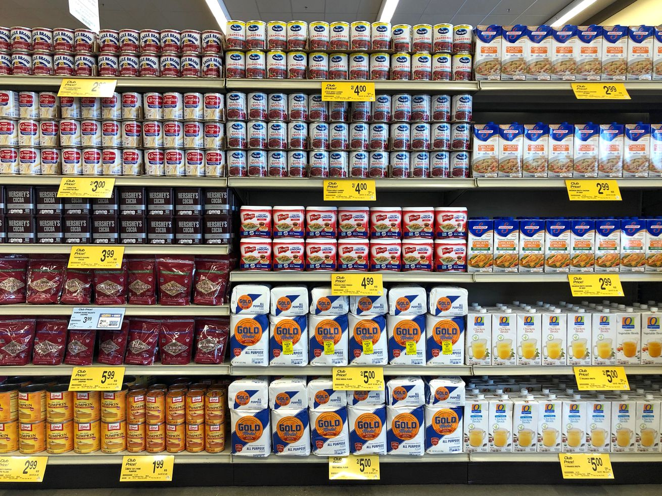 Grocery store shelves with cans of condensed milk, chocolate, pumpkin puree, cranberry sauce, flour