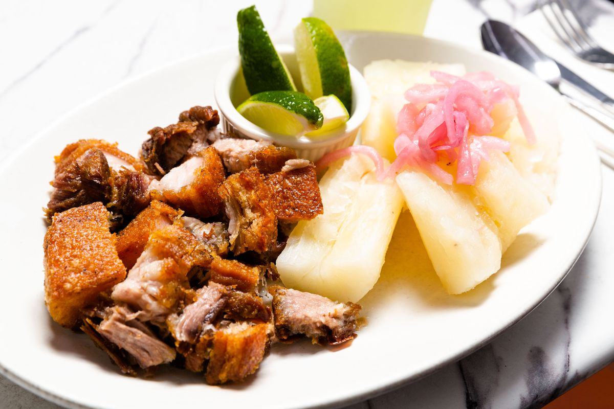 Nuggets of chicarron Dominicano sit next to yucca on a white plate with pickles