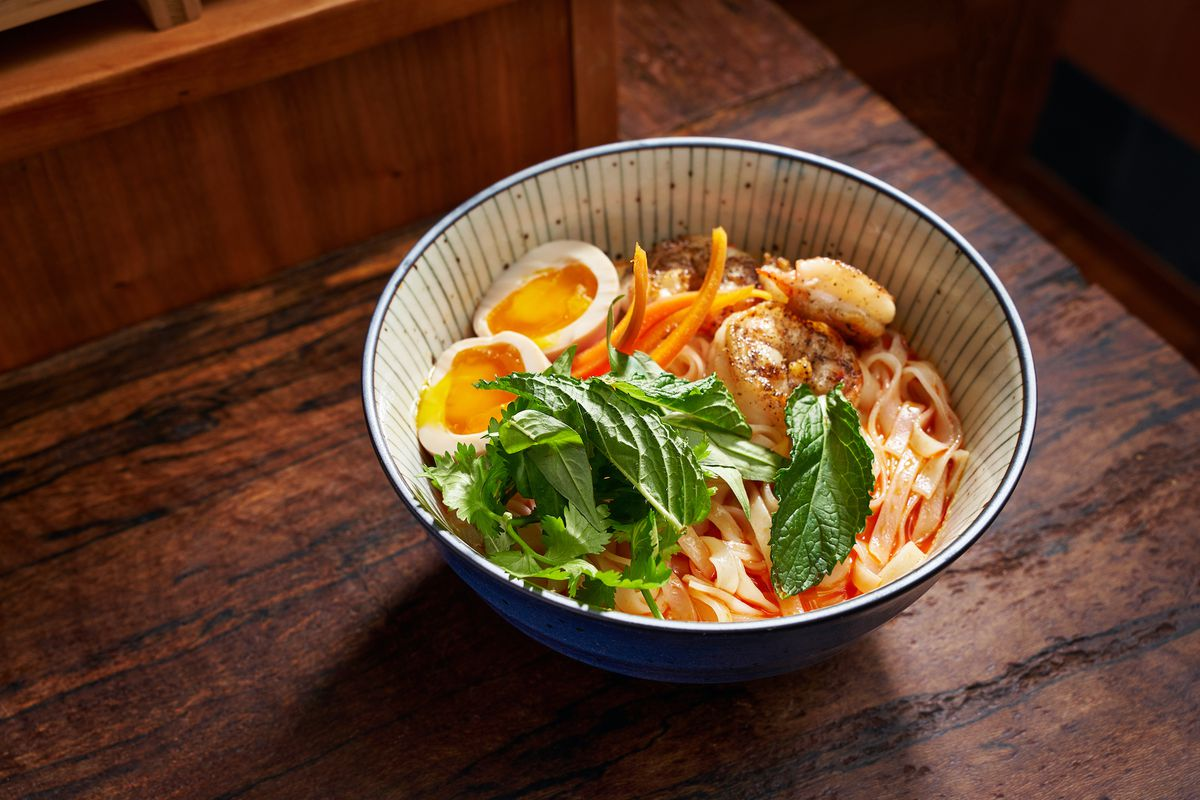 A bowl of soup with noodles, basil leaves, soft boiled eggs sliced in half placed on a wooden table