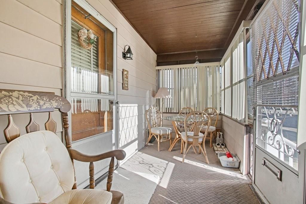 A screened-in front porch with a front door.