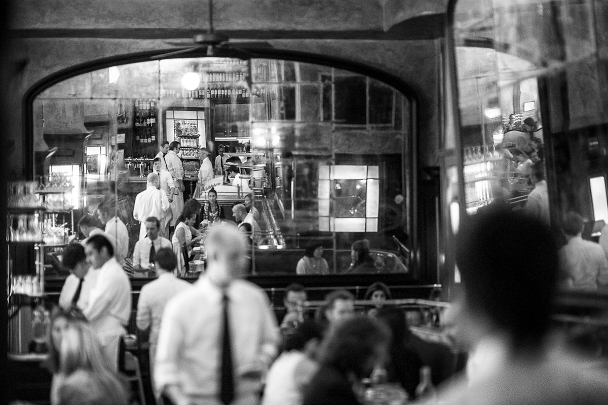 A black and white photo of a server making the rounds inside the French brasserie Balthazar