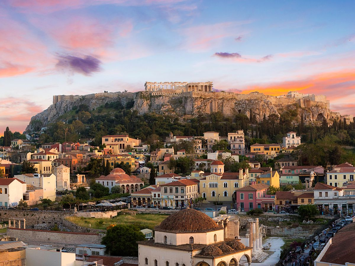 An aerial view of Athens in Greece. There are multitudes of houses perched on a mountain side. On top of the mountain are historic buildings. There is a sunset in the sky.