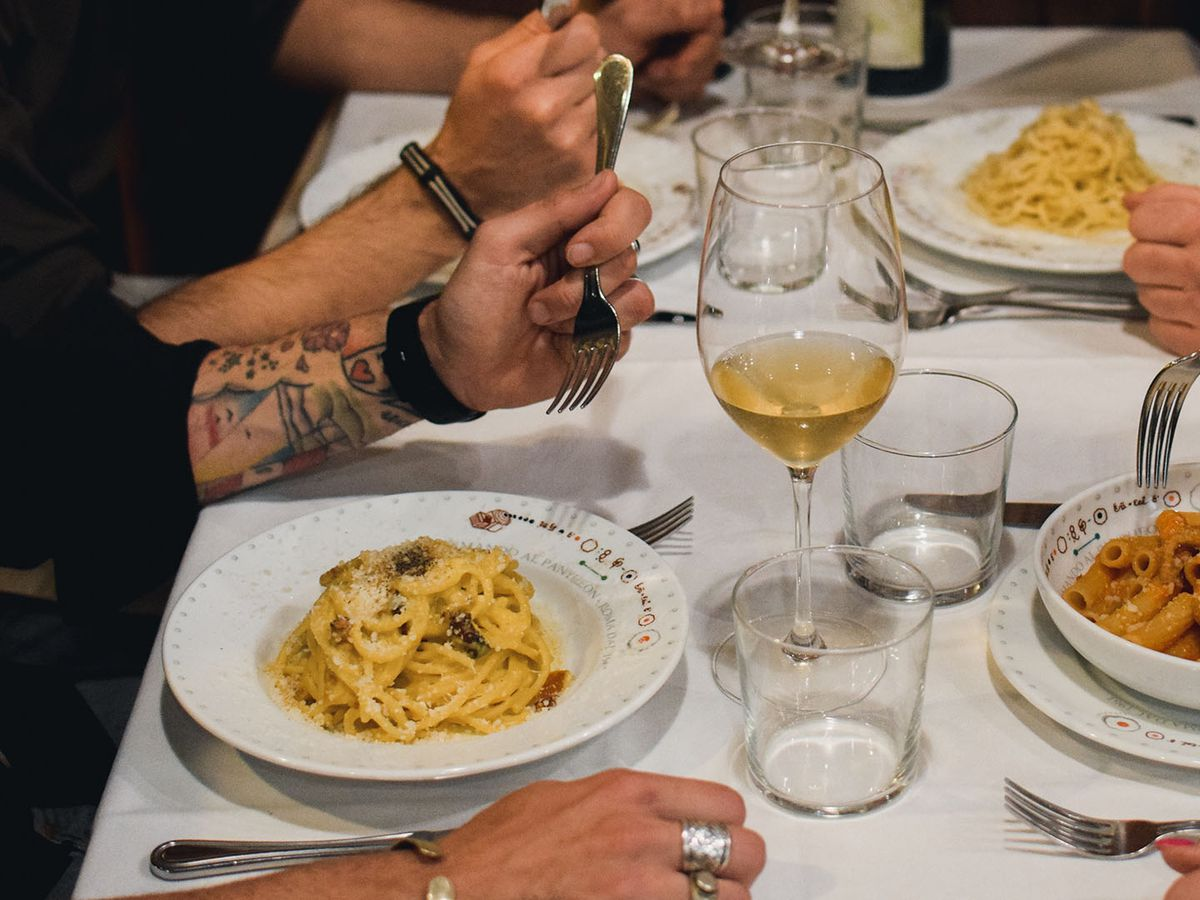 Four diners eat pasta and drink wine at a white table cloth-covered table