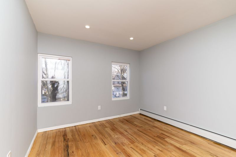 A bedroom with grey walls, hardwood floors, and two small windows.