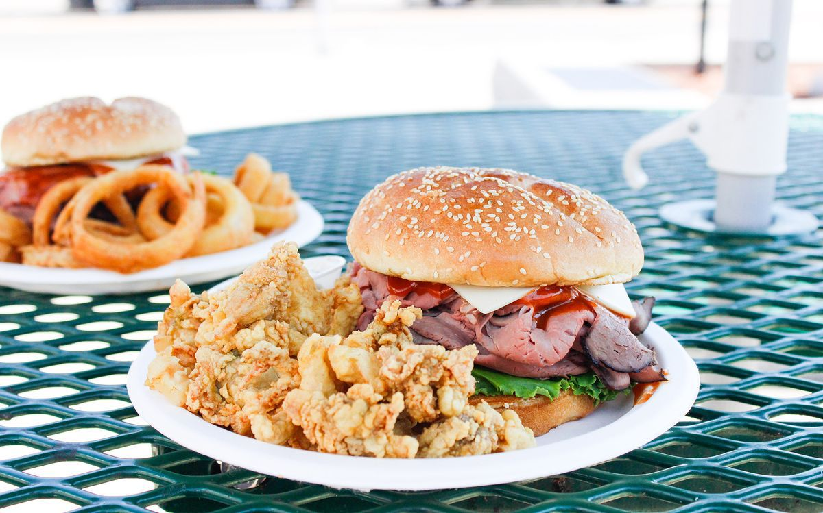 Roast beef sandwich and a side of fried clams on a picnic table. Another sandwich with onion rings is visible in the background.
