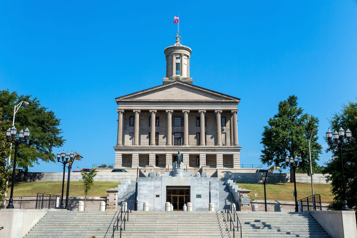 The exterior of the Tennessee State Capitol.  The facade is tan. There are columns on the front of the building. There is a tower with a flagpole on top.