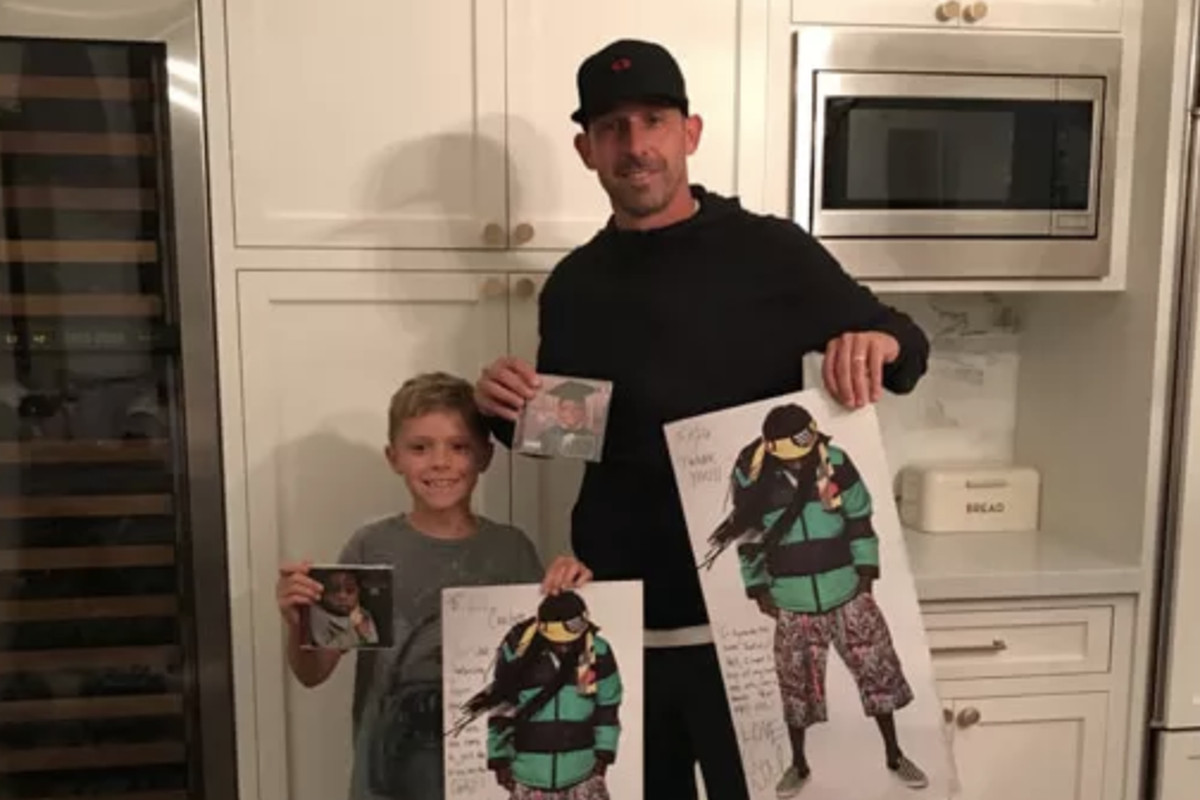 Kyle Shanahan and his son holding up Lil Wayne merchandise