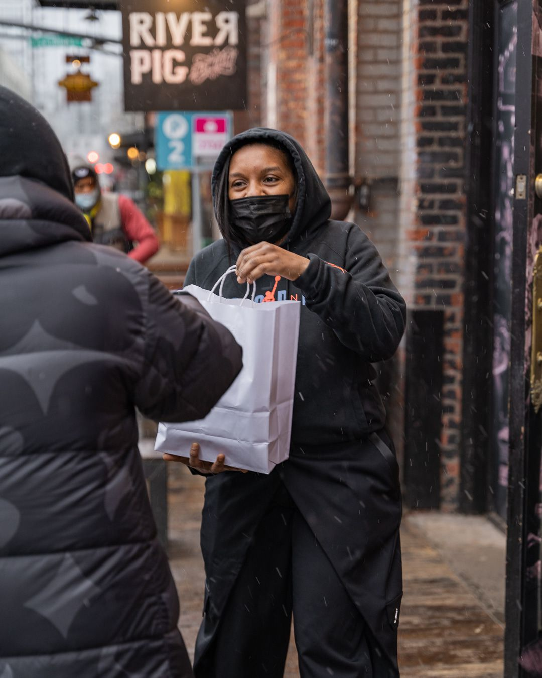 A woman in a black mask and hoodie holds out a white paper bag to a person in a parka.