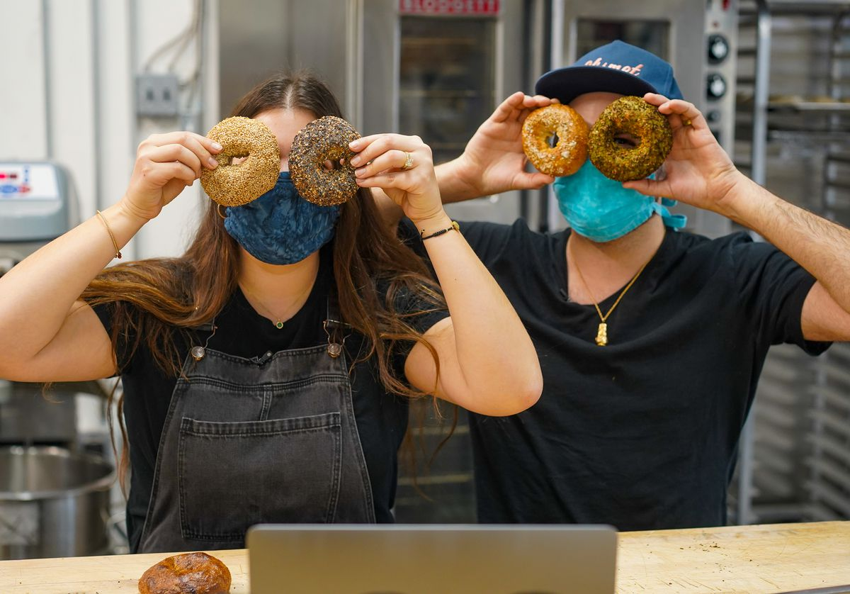 a man and a woman hold up bagels over their eyes in bakery