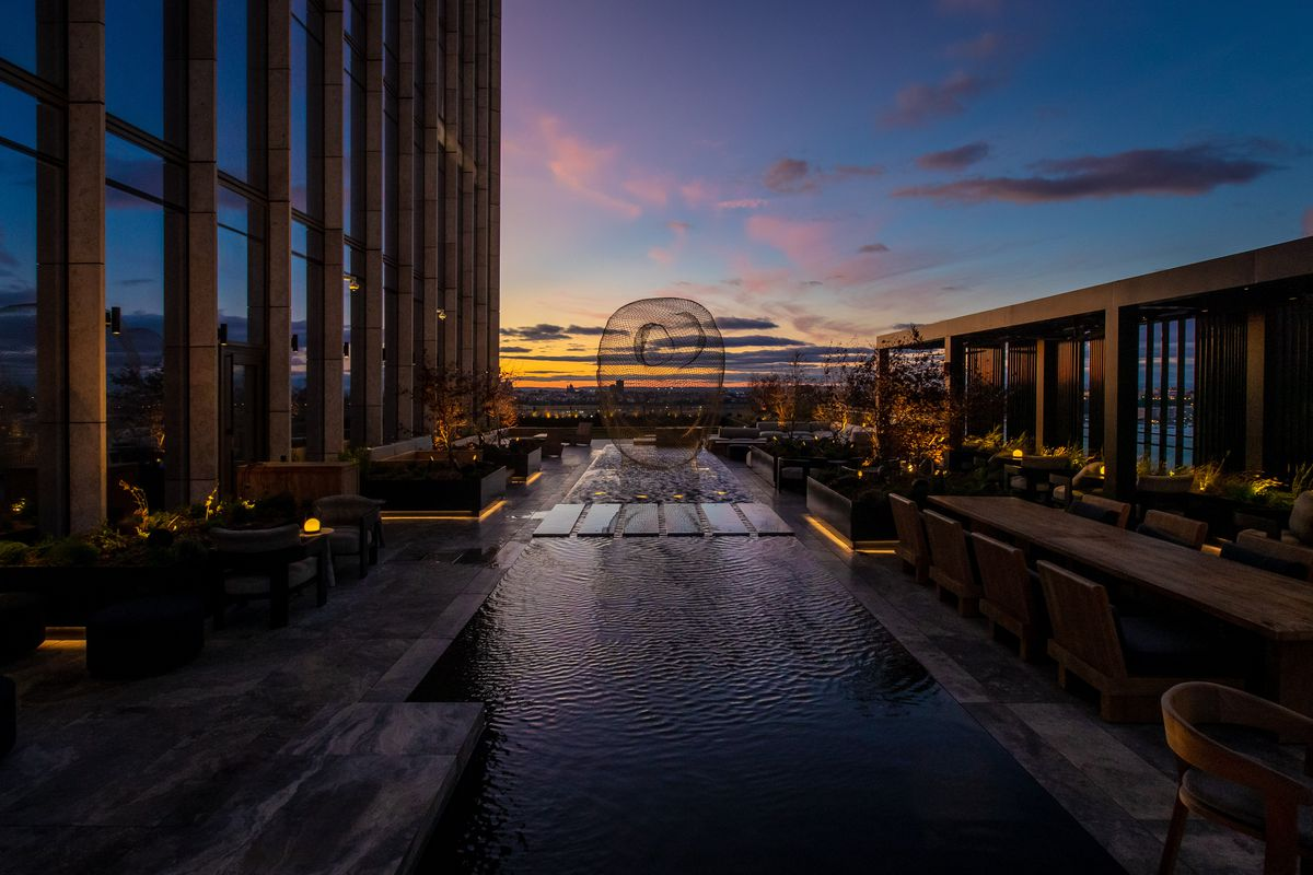 The sun sets behind the Hudson at Electric Lemon's outdoor terrace, decked out with a rectangular reflecting pool
