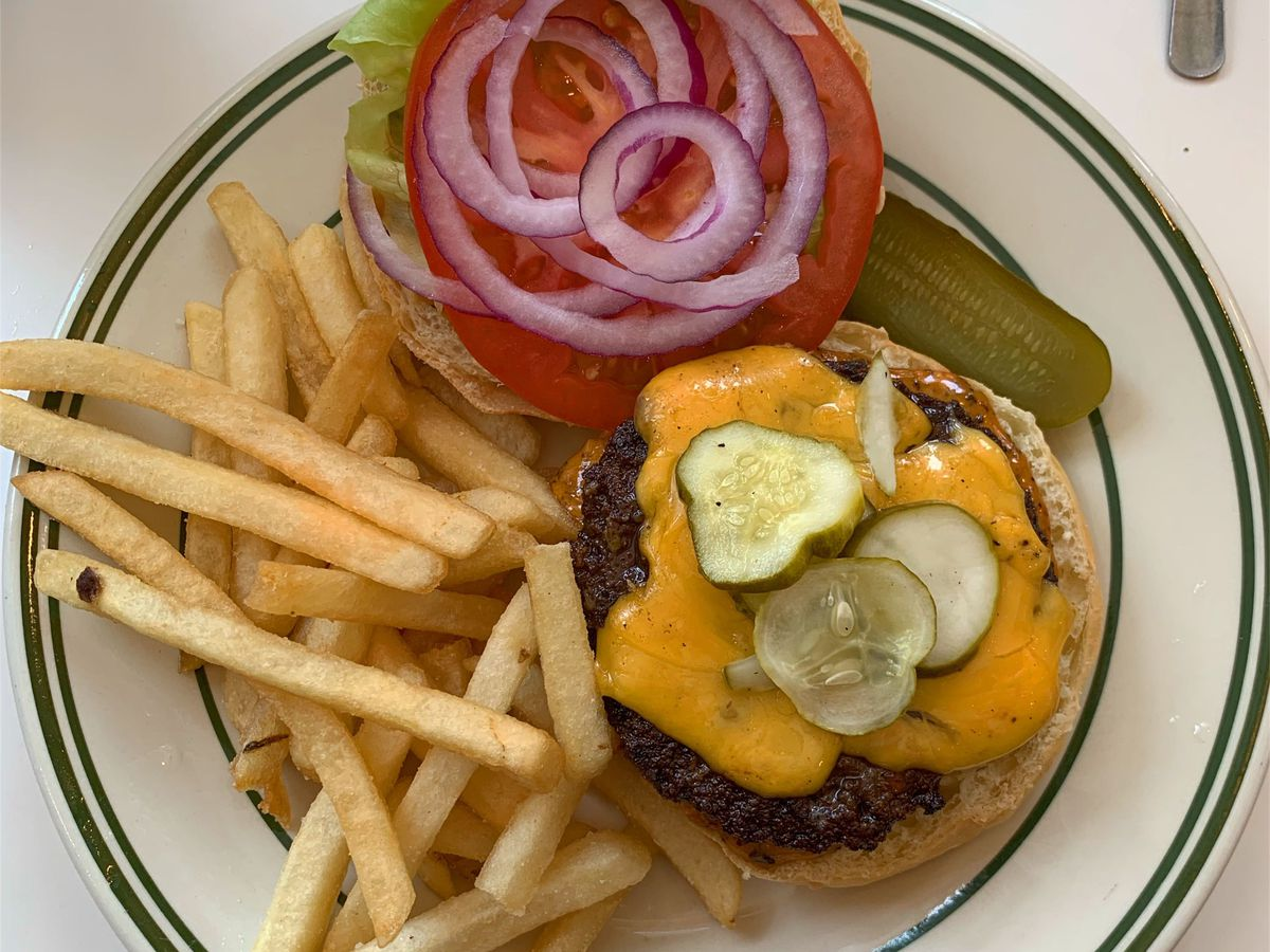 A cheeseburger with three pickles on top, plus fries, on a white plate with a striped lining.