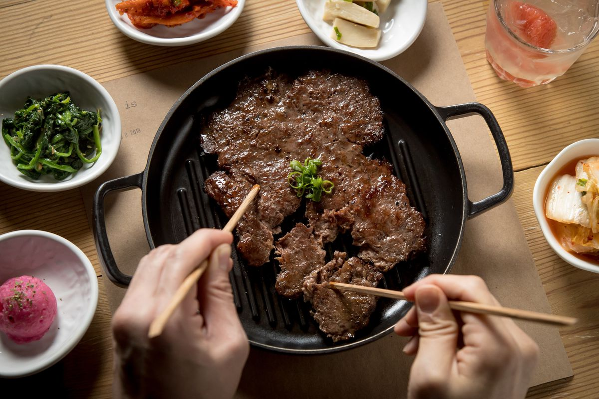 Fire-grilled bulgogi, being pulled apart by chopsticks