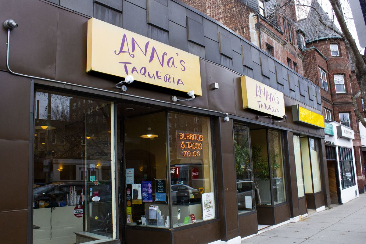 """Exterior of a casual burrito shop. The outer wall is dark brown, and the signage is pale yellow, with """"Anna's Taqueria"""" written in red in a distinctive scrawling font."""